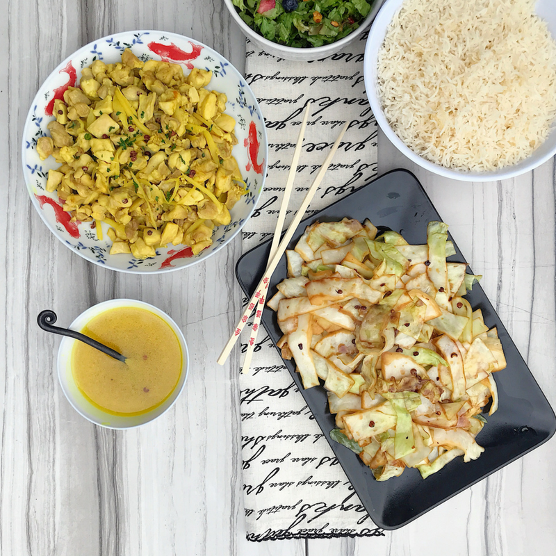 An aerial view of ginger chicken with spicy steamed cabbage, with rice and a salad. Chopsticks are displayed next to the thin-cut cabbage.