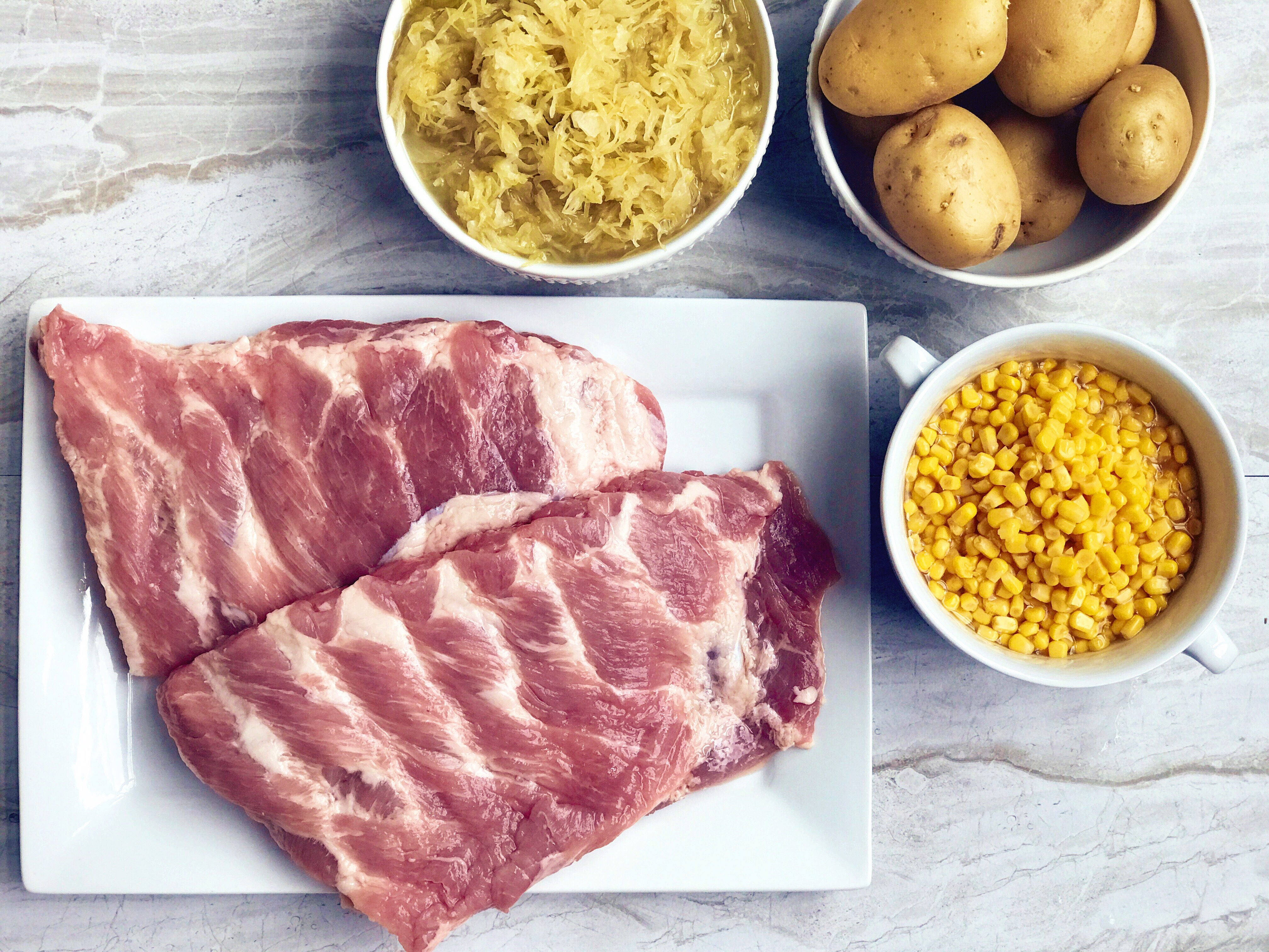 An image of some of the ingredients needed to make German Sauerkraut and Spareribs: pork spare ribs, corn, potatoes, and sauerkraut.