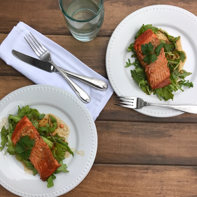 Two servings of sweet orange salmon are displayed next to each other, with cutlery resting on top of a white napkin sitting between the two plates. A glass of water is displayed as well.
